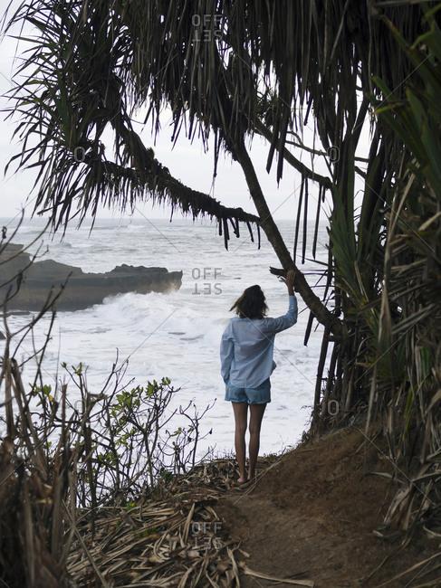 Young woman walking at ocean coastline