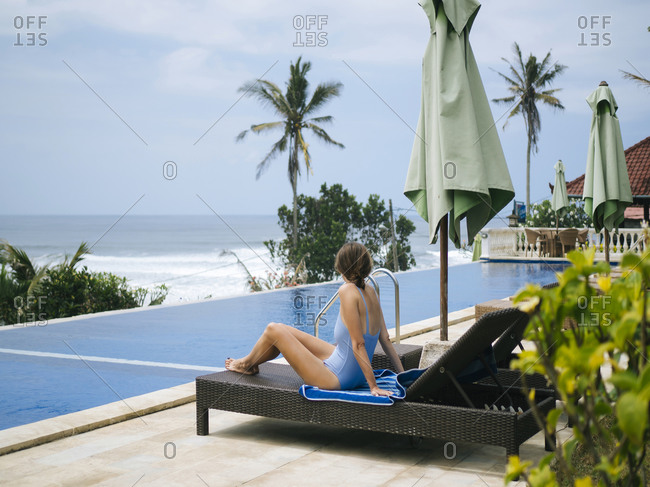 Woman sunbathing lounge chair poolside