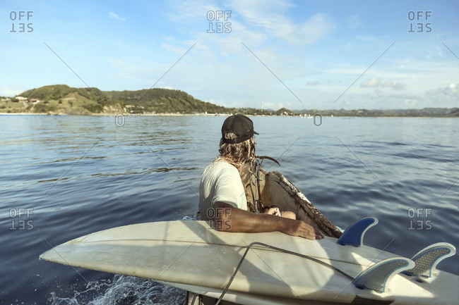 Unrecognizable surfer riding boat at sunny day