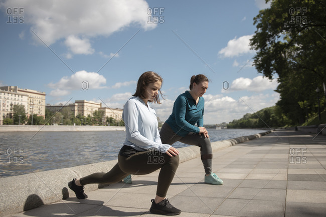 Two young women doing stretching exercise outdoors during sunny day