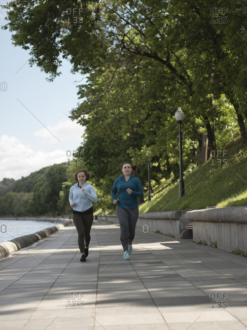 Two young women jogging by the riverside in city park during sunny day