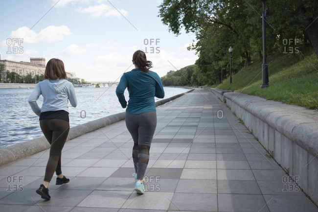 Rear view of two young women jogging by the riverside in city park