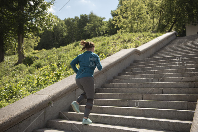 Rear view of woman running on steps in city park during sunny day