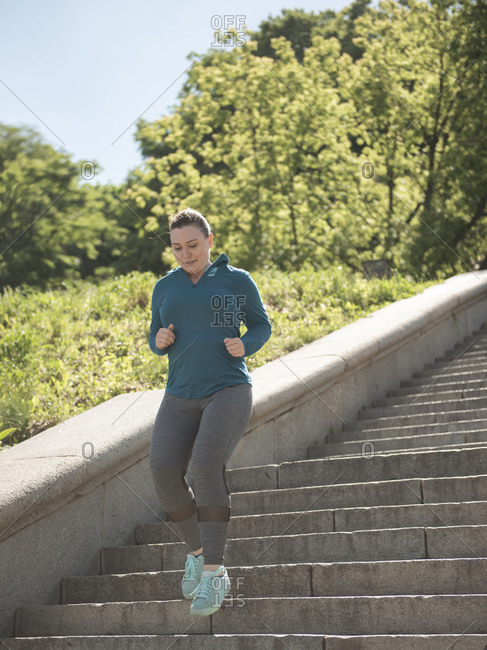 Young woman running on steps in city park during sunny summer day