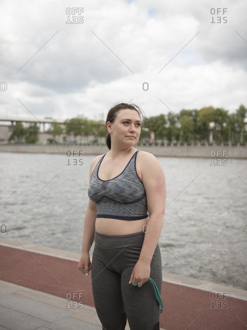 Woman in sportswear standing on riverside after workout against sky