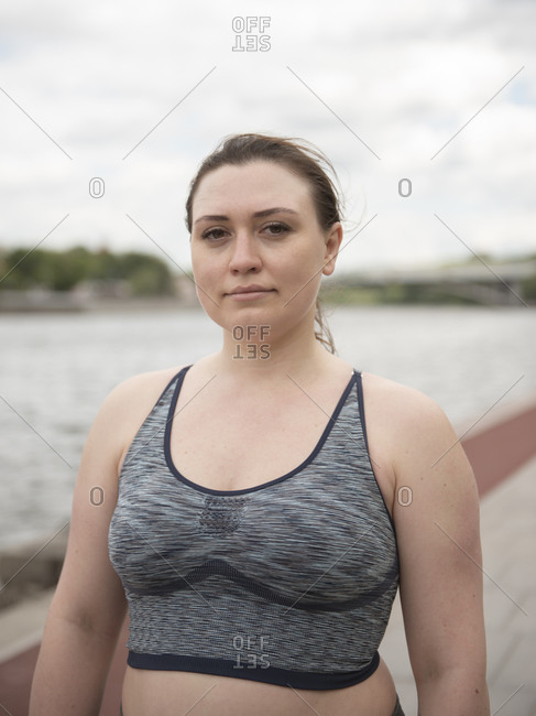 Woman in sportswear standing and looking at camera against cloudy sky