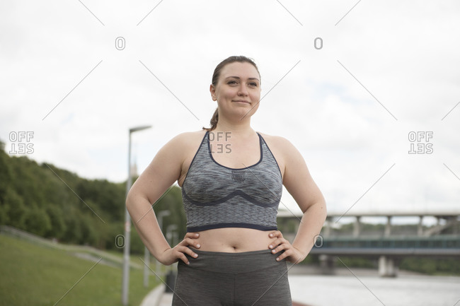 Woman with hands on hips in sportswear standing and looking away