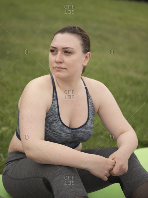 Woman get some rest after workout and sitting on mat against grass