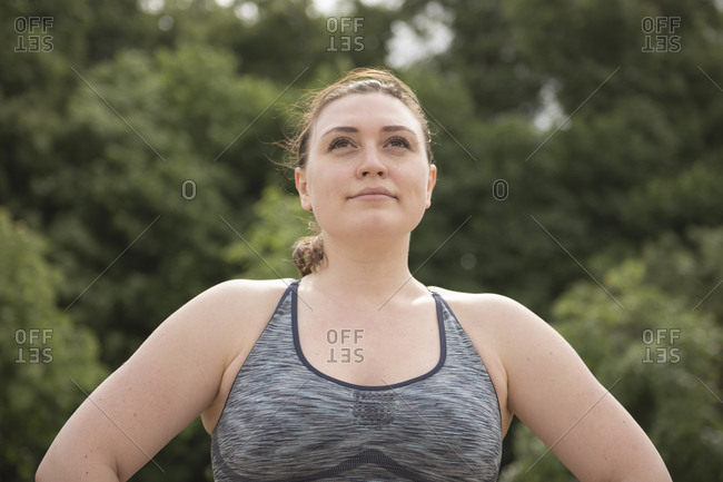 Woman in sportswear looking far away against trees during summer day