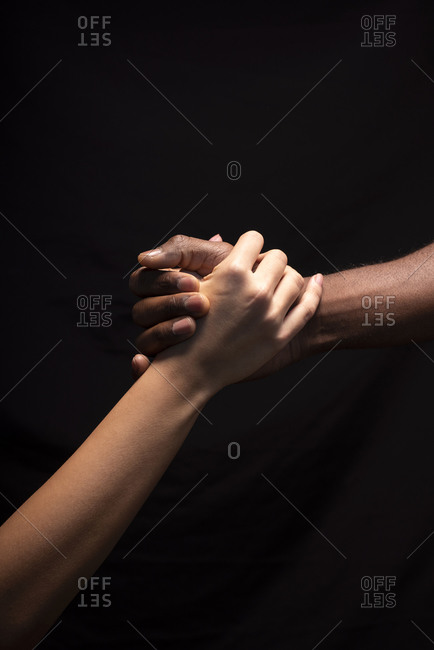 Male and female hands with different skin tones holding each other
