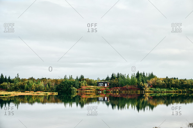 Tranquil landscape of lonely house among forest on coast of lake