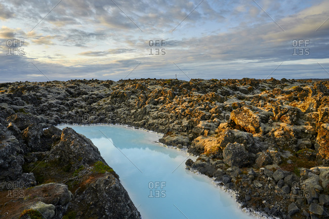 Picturesque landscape of geothermal spring in rocky terrain at sunset