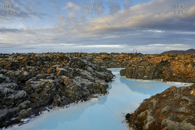 Scenic view of blue lagoon with volcanic shore in cloudy day