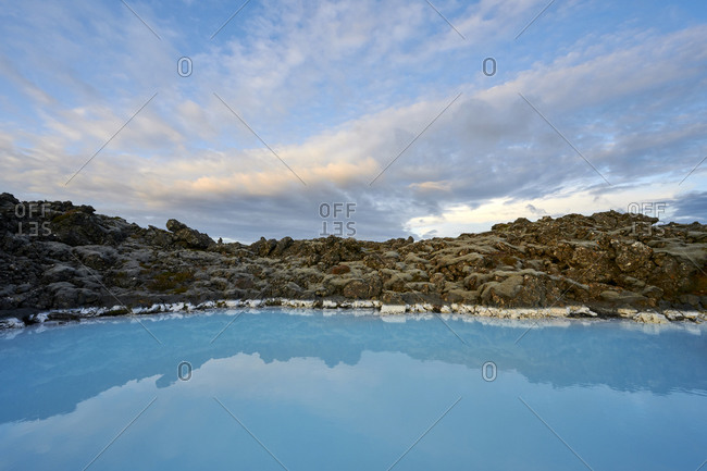 Scenic landscape of geothermal lagoon with rocky shore in cloudy day