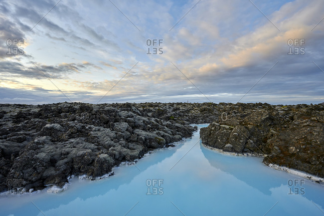 Scenic landscape of cloudy sky over blue lagoon at sunset
