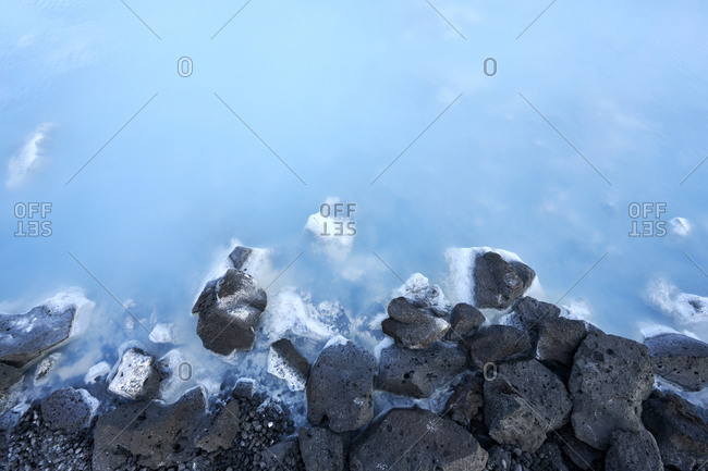 Natural geothermal lake with stony coast