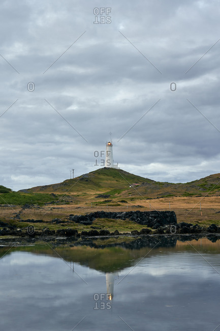 Picturesque scenery of lonely beacon under cloudy sky