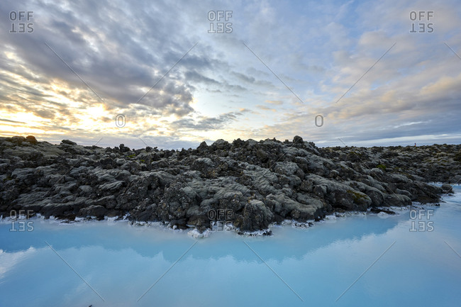 Picturesque scenery of geothermal lake with rocky coast at sunset