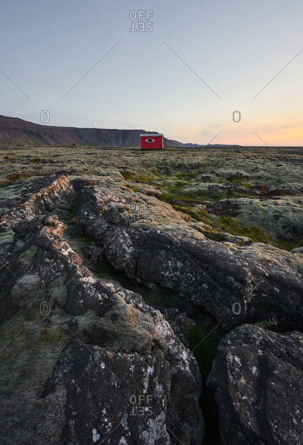 Picturesque landscape of shack on volcanic terrain at sundown