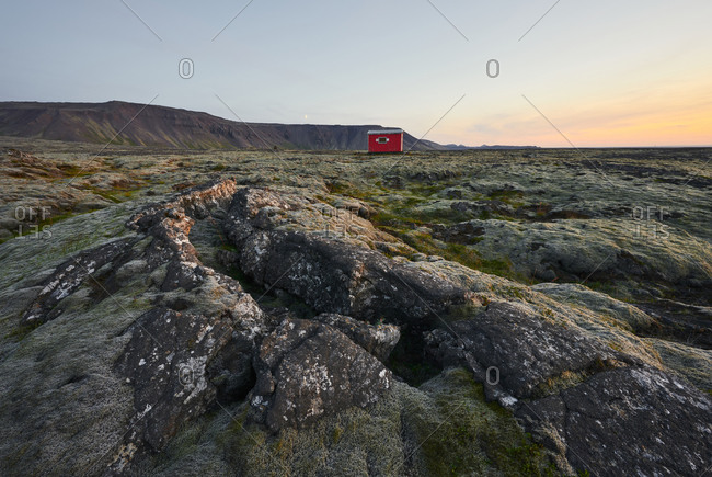 Scenic landscape of rocky location with cabin at sunset