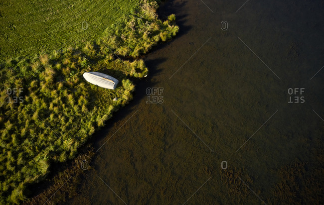Wonderful view of solitary white wooden boat drying out on grassy beach of river