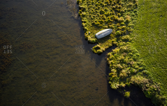 Solitary wooden boat drying out on river shore