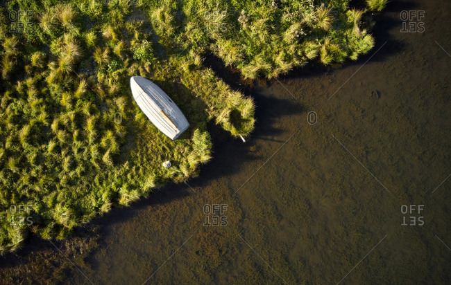 Solitary wooden boat lying on river shore