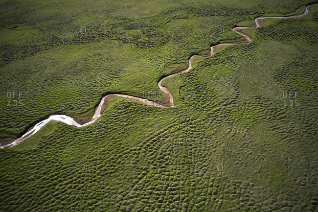 Amazing aerial landscape of flowing stream in green field