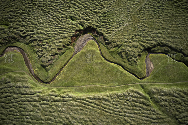 Aerial landscape of winding dry river in green field