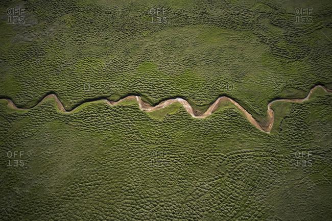 Dry river geometrically flowing in green field
