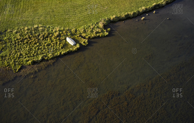 White wooden boat drying out on grassy beach of tranquil river