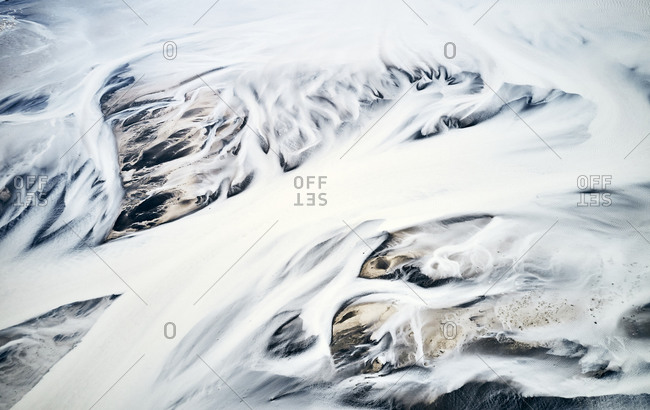 Streams of snow covering mountainous land below