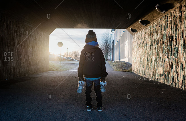 Young boy standing in a tunnel holding his ice skates in winter