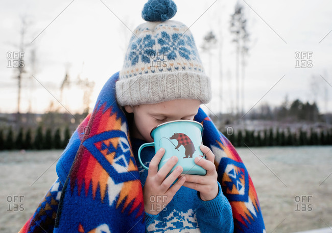 Young boy wrapped in a blanket drinking hot chocolate outside