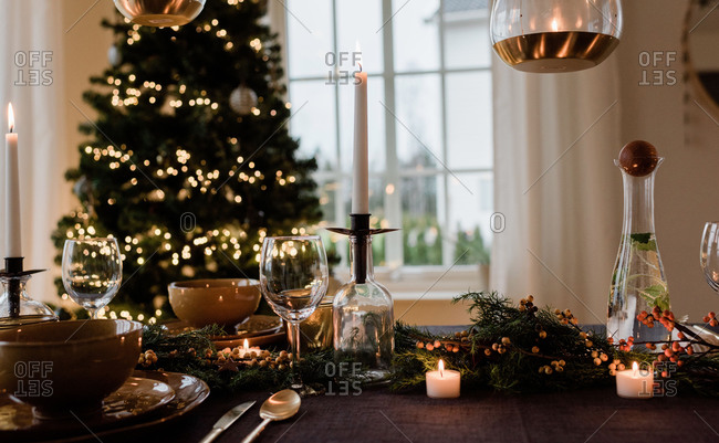Tall candle on a festively decorated dinner table at Christmas