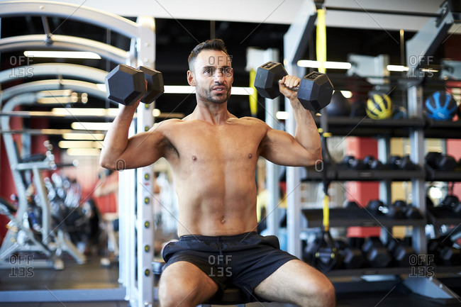 A man doing shoulder exercises at the gym.