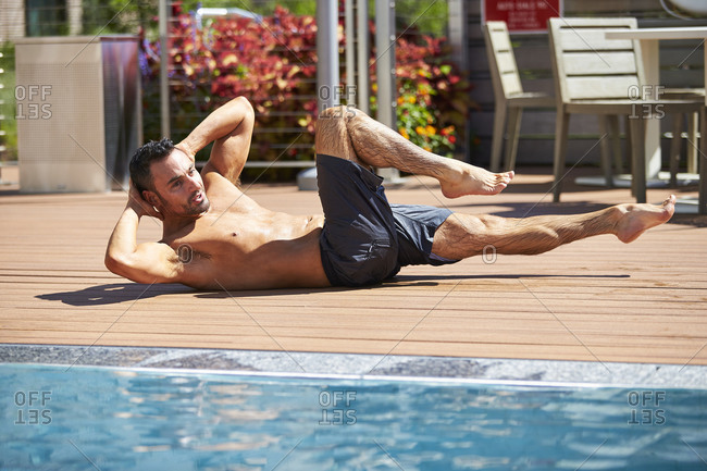A fit man doing crunches by the pool.