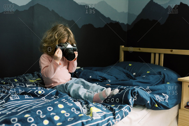 A little girl playing with a camera.