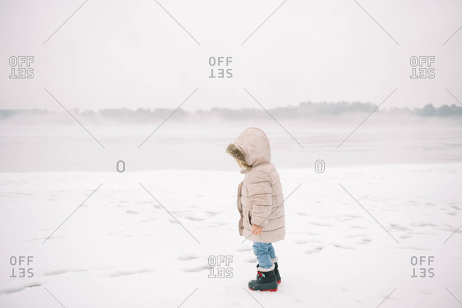 Little girl standing in the rain on an icy beach.