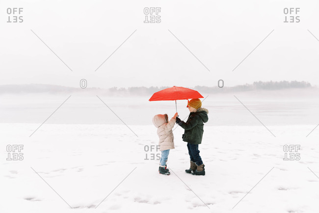 A brother and sister having fun in the wintery rain.