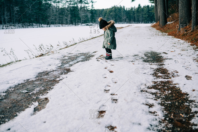 Little girl staring at her feet amidst the snow.