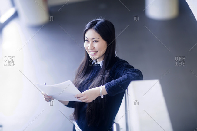 Young Asian woman with paper in an office standing with paper