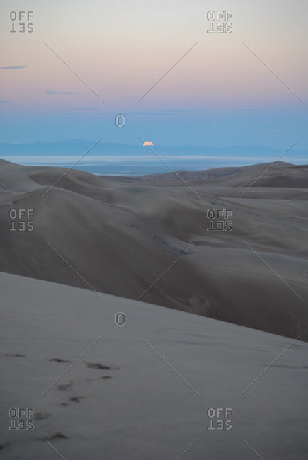 Moon dipping below mountains in sand dunes
