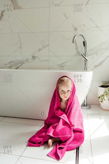 Little girl sitting on the floor in the bath in a pink towel