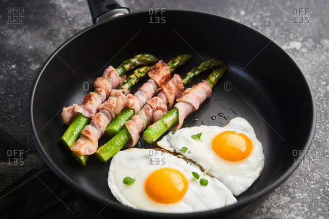 Close up of asparagus wrapped in bacon with eggs in a skillet