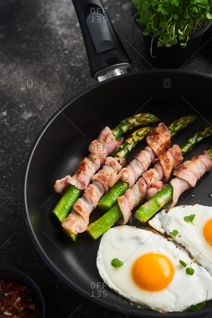 Close up of bacon wrapped asparagus with eggs in a skillet