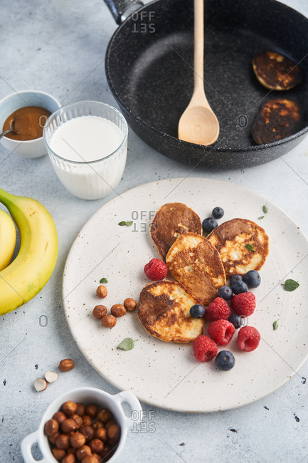 Pancakes with fruit beside a frying pan with a wooden spatula