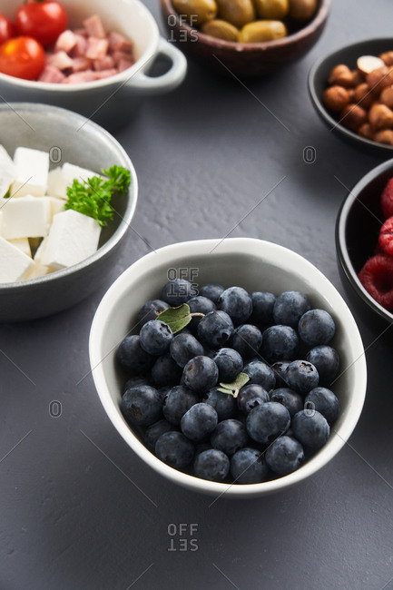 Berries and other ingredients in dishes on a gray background