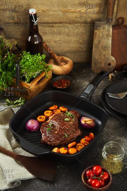 Juicy steak on a skillet with veggies