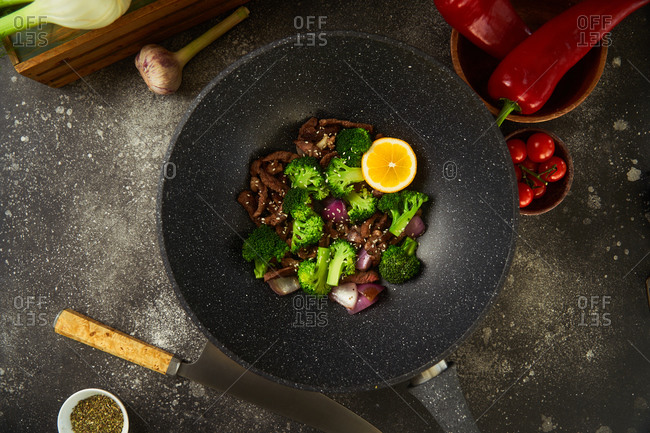 Top view of a beef and vegetable dish being prepared in a wok